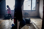 """A chained dog and the daughter of Milena in their flat at the concrete building """"Hrebenova 34-36"""" which was in an appalling condition and demolished in August 2014 by the city of Kosice. The family of Milena, her mother Bozena and their children had been one of the last families living in that building waiting for a compensatory flat which they received a short while later. They belonged among the 5% of inhabitants of that building which had a renting contract, were paying rent and with that the right to get a new flat at the housing estate."""