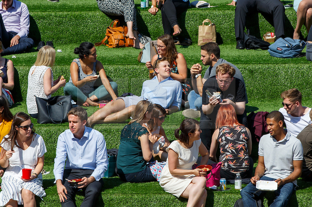 © Licensed to London News Pictures. 17/08/2016. London, UK. People enjoy hot weather on their lunch breaks in Granary Square, King's Cross, London on Wednesday, 17 August 2016. Photo credit: Tolga Akmen/LNP