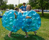 """Katelyn Pinter and """"Wish Kid"""" Charlotte Larochelle try a little Sumo Bubble Wrestling with """"Wish Kid"""" Eric Adams as referree during the Make A Wish event at Hesky Park on Saturday afternoon.  (Karen Bobotas/for the Laconia Daily Sun)"""