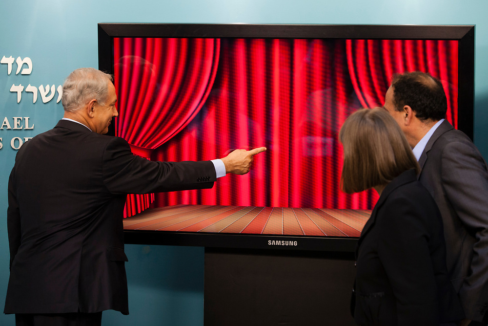 Israel's Prime Minister Benjamin Natanyahu (L) uses his finger to unveil a new virtual exhibition on the 'Google Cultural Institute' about former Israeli Prime Minister Menachem Begin, during the launch of the new exhibition, at the Prime Minister's Office in Jerusalem, Israel, on September 16, 2013.
