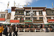 Pilgrims and tourists pass vendors selling traditional Buddhist items on the Barkor at the Jokang Monastery, Lhasa, Tibet.
