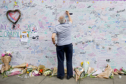 A man writes a tribute on a wall near Latimer Road, close to Grenfell Tower in west London after a fire engulfed the 24-storey building on Wednesday morning.