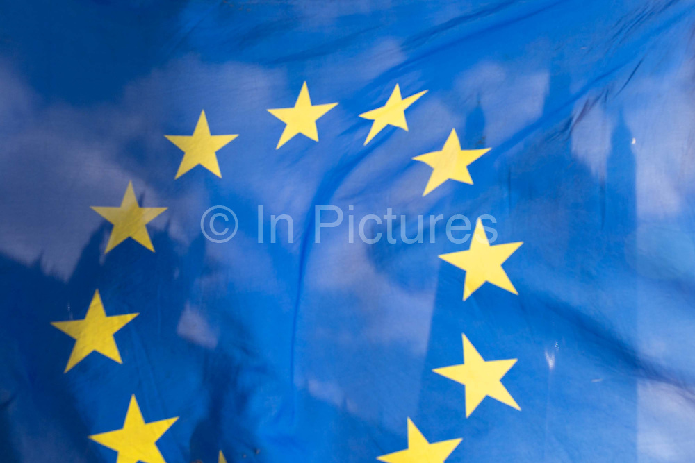 As Prime Minister Theresa May negotiates further Britains exit from the European Union in Brussels, the UK parliament is seen through the yellow stars of the EU flag, flying as part of an anti-Brexit protest opposite the Houses of Parliament, on 7th February 2019, in Westminster, London England.