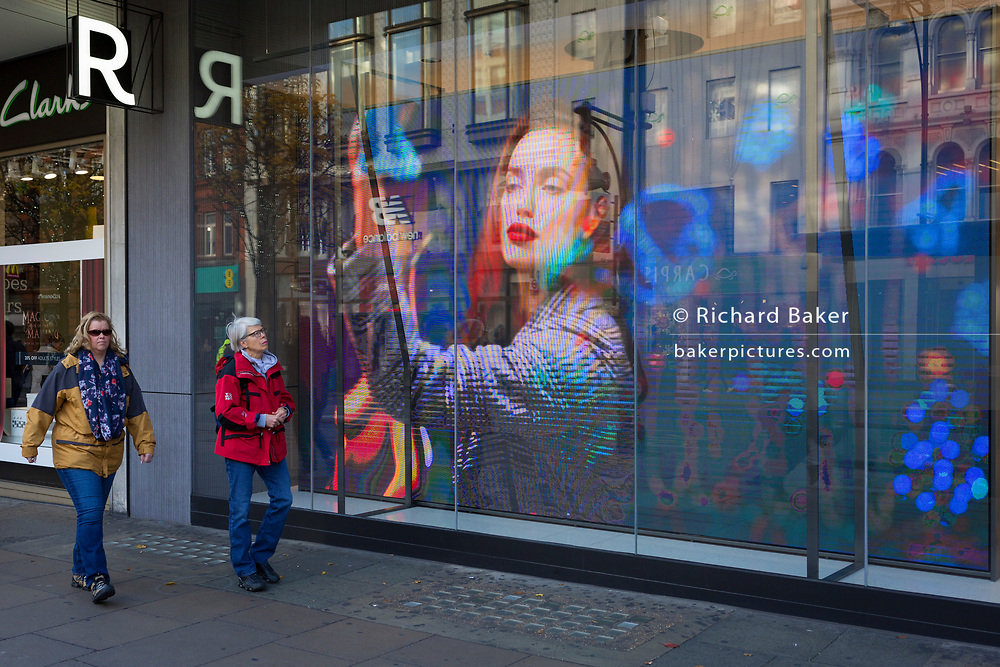 Pre-Christmas shoppers walk past a video ad loop for the London retailer 'Reserved', on Oxford Street, on 23rd November 2017, in London England.