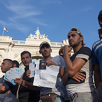 Illegal migrants hold their valid train tickets complaining they were denied travel to Germany at the main railway station Keleti in Budapest, Hungary on September 02, 2015. ATTILA VOLGYI