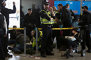 As environmental activists protest about Climate Change during the occupation of City Airport (London's Business Travel hub) in east London, police officers process the arrested inside the termional building on the fourth day of a two-week prolonged worldwide protest by members of Extinction Rebellion, on 10th October 2019, in London, England.