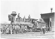 """RGS 2-8-0 #16 in for repairs posing with Durango shop crew.  Notice the damaged cab and tender front from a collision with cars at Durango smelter.<br /> RGS  Durango, CO  Taken by Root, George - ca 1902<br /> In book """"Narrow Gauge Country 1870-1970"""" page 104<br /> Cropped version of RD155-031 except a lighter image.<br /> Also in """"Silver San Juan"""", p. 111."""