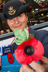 Covent Garden, London, October 30th 2014. They Royal British Legion's Poppy Day in London centred around Covent Garden where bands, choirs, classical and pop musicians entertained crowds as Air Force personnel carrying donation buckets sold poppies, hoping to raise in excess of £1 million. Pictured: An air Force officer offers a poppy.