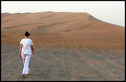A lady walks through the sand dunes in Dubai, UAE. Photo By Andrew Parsons/i-Images.