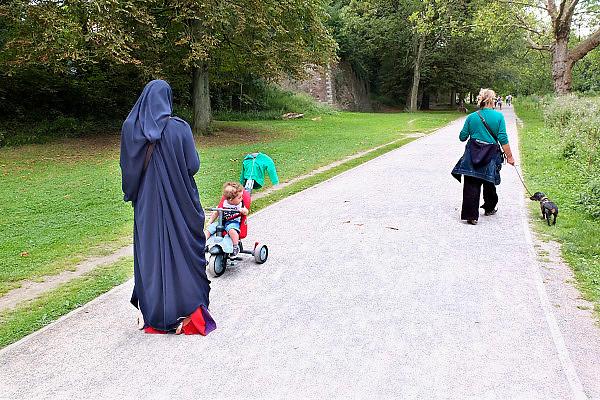 Frankrijk, Lille, 18-8-2013Lille ligt in een sterk de verarmde regio noordwest. Het is de hoofdstad van Frans Vlaanderen, van de regio Nord Pas de Calais en van het Noorder departement. Park rond de citadel. Een moslim vrouw met kind en een westerse vrouw met hond. Sluier,gesluierd,gesluierde, moslims,moslima.Foto: Flip Franssen/Hollandse Hoogte