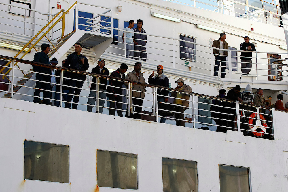 Indian and Bangladeshi nationals stand on the deck of the ferry MV Red Star One as it arrives at Valletta's Grand Harbour March 6, 2011.  The Indian-chartered ferry arrived in Malta from Misurata in Libya on Sunday morning carrying 301 evacuees, mostly Indians but also including Filipino, British and Bangladeshi nationals...REUTERS/Darrin Zammit Lupi (MALTA)