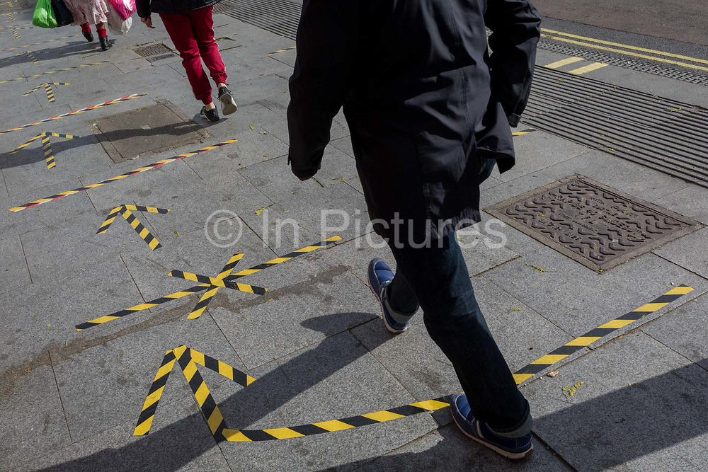 The day after UK Prime Minister Boris Johnson addressed the nation with his roadmap for the coming weeks and months during the Coronavirus pandemic lockdown, south Londonerss feet and legs pass over the now worn hazard tape that marks out safe social distancing practice at East Street Market on the Walworth Road, on 11th May 2020, in London, England.
