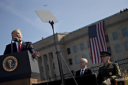 September 11, 2017 - Washington, District of Columbia, United States of America - United States President Donald J. Trump, left, speaks as General Joseph Dunford, Chairman of the Joint Chiefs of Staff, right and Jim Mattis, US Secretary of Defense, listen, during a ceremony to commemorate the September 11, 2001 terrorist attacks, at the Pentagon in Washington, D.C., U.S., on Monday, Sept. 11, 2017. Trump is presiding over his first 9/11 commemoration on the 16th anniversary of the terrorist attacks that killed nearly 3,000 people when hijackers flew commercial airplanes into New York's World Trade Center, the Pentagon and a field near Shanksville, Pennsylvania. .Credit: Andrew Harrer / Pool via CNP (Credit Image: © Andrew Harrer/CNP via ZUMA Wire)