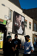 Hackney Carnival on 8th September 2019 in London, United Kingdom. On Morning Lane, men stand under a poster advertising the TV programme, Top Boy.