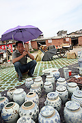 A vendor shades himself from the sun as he sells antique peices of porcelain in the Gao Mao Market of Jingdezhen June 26, 2006.