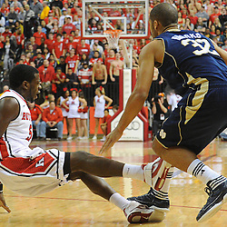 Rutgers Scarlet Knights guard Eli Carter (5) draws a charging foul on Notre Dame Fighting Irish guard Joey Brooks (32) during Big East NCAA action during Rutgers' 65-58 victory over Notre Dame at the Louis Brown Athletic Center in Piscataway, N.J.