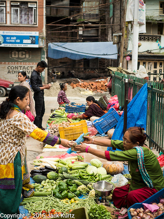 06 AUGUST 2015 - KATHMANDU, NEPAL: A produce market in central Kathmandu with a home destroyed in the earthquake in the background. The Nepal Earthquake on April 25, 2015, (also known as the Gorkha earthquake) killed more than 9,000 people and injured more than 23,000. It had a magnitude of 7.8. The epicenter was east of the district of Lamjung, and its hypocenter was at a depth of approximately 15km (9.3mi). It was the worst natural disaster to strike Nepal since the 1934 Nepal–Bihar earthquake. The earthquake triggered an avalanche on Mount Everest, killing at least 19. The earthquake also set off an avalanche in the Langtang valley, where 250 people were reported missing. Hundreds of thousands of people were made homeless with entire villages flattened across many districts of the country. Centuries-old buildings were destroyed at UNESCO World Heritage sites in the Kathmandu Valley, including some at the Kathmandu Durbar Square, the Patan Durbar Squar, the Bhaktapur Durbar Square, the Changu Narayan Temple and the Swayambhunath Stupa. Geophysicists and other experts had warned for decades that Nepal was vulnerable to a deadly earthquake, particularly because of its geology, urbanization, and architecture.      PHOTO BY JACK KURTZ