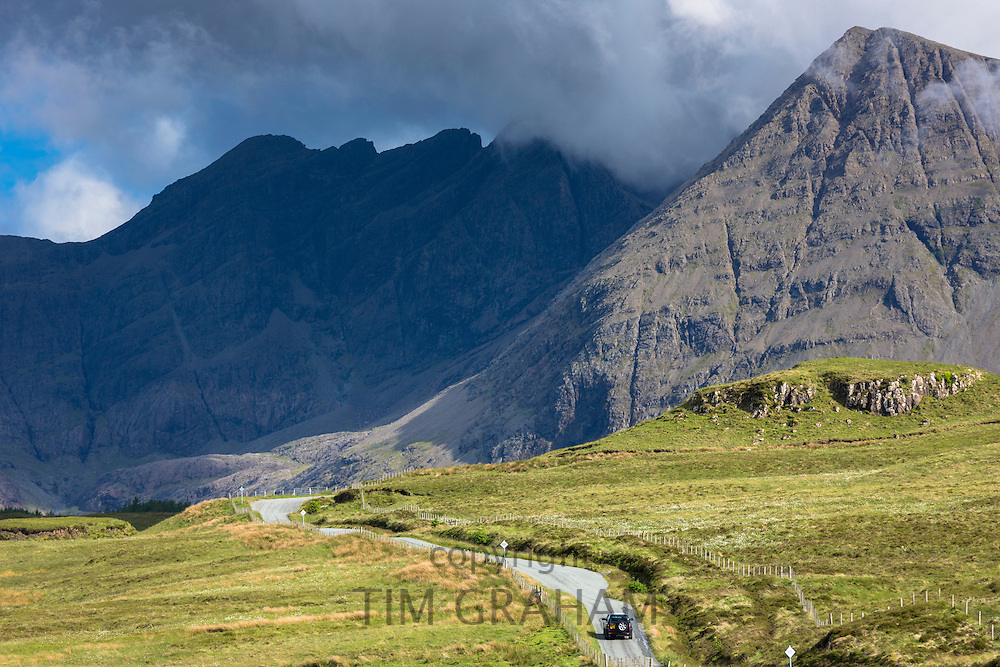 4x4 4-wheel drive vehicle by Cuillin mountain range on Isle of Skye in the Highlands and Islands of Scotland