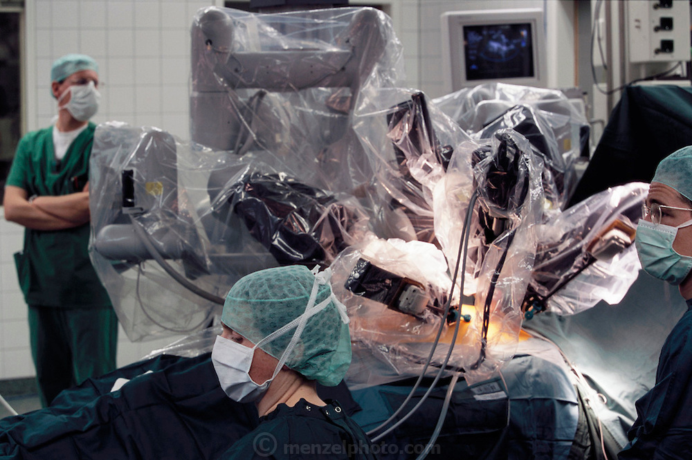Dr. Volkmar Falk performs robotic surgery on a patient from controls in the next room at the Herzzentrum Heart Center in Leipzig, Germany. (Visiting doctors watch surgeon Volkmar Falk perform a coronary artery bypass graft on a patient lying in the adjoining room, using a tele-manipulated surgical system (called a robotic system by some) designed by Intuitive Surgical Corporation of Mountainview, California, at the Herzzentrum, Leipzig, Germany. The assistant surgeon has incised small holes into the patient's chest wall through which the instruments-attached to sterile plastic covered manipulating arms-will pass and be telemanipulated by the surgeon in the next room. The room in which the surgeon is working is a less sterile work environment than that of the operating room where the patient lies. It is much like an office; phones are ringing, there is heavy foot traffic and personal conversation-at times at crescendo level.