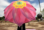 """pvcPESCADO1/6-8-06/JP2/ASEC.  Audrey Pennington (CQ), holding an umbrella is accompanied by her two daughters Luisa Pennington (CQ) age 7, and justine Pennington (CQ) age 5, not pictured, watch as a large crane lifts a 7,000 pound (The artist's son Scot Furgason said it was 7,000 pounds, Not 12,000 pounds as the press release stated) sculpture entitled """"Fish Globe"""" created by Santa Fe artist Colette Hosmer, off a flat bet trailer at Tingley Beach, photographed Thursday June 8, 2006.  (PAT VASQUEZ-CUNNINGHAM/JOURNAL)"""
