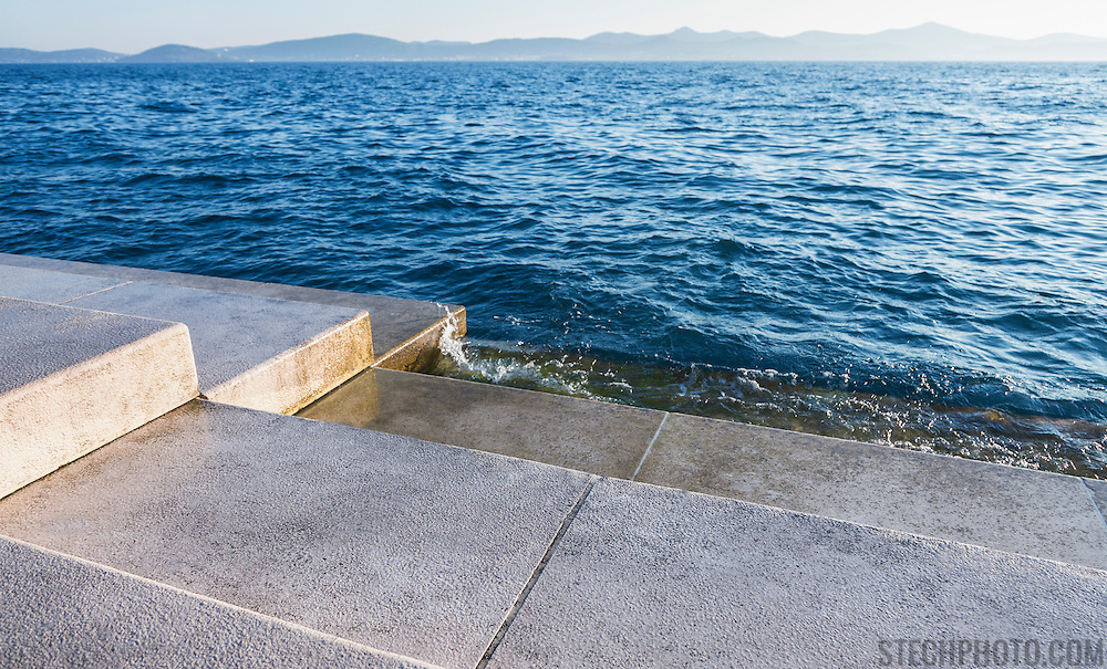 The steps of the Sea Organ in Zadar, Croatia where land meets the water (Adriatic Sea). Designed by architect Nikola Basic, 35 organ pipes are built under the steps so that the wind and water from the sea create musical sounds.<br /> <br /> LICENSING: This image can be licensed through SpacesImages. Click on the link below:<br /> <br /> http://tinyurl.com/c55uggt