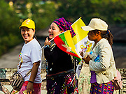 27 NOVEMBER 2017 - YANGON, MYANMAR: Myanmar women, one in traditional dress, walk to the train station after seeing Pope Francis in Yangon. Pope Francis arrived in Yangon Monday for a four day / three night visit. Tuesday he is going to the capitol, Naypyidaw (Nay Pyi Taw) to meet with Aung San Suu Kyi and other Myanmar leaders. Wednesday and Thursday he is saying mass in Yangon and on Thursday afternoon he is going to neighboring Bangladesh. There are around 450,000 Catholics in Burma, about 1% of the total population.   PHOTO BY JACK KURTZ