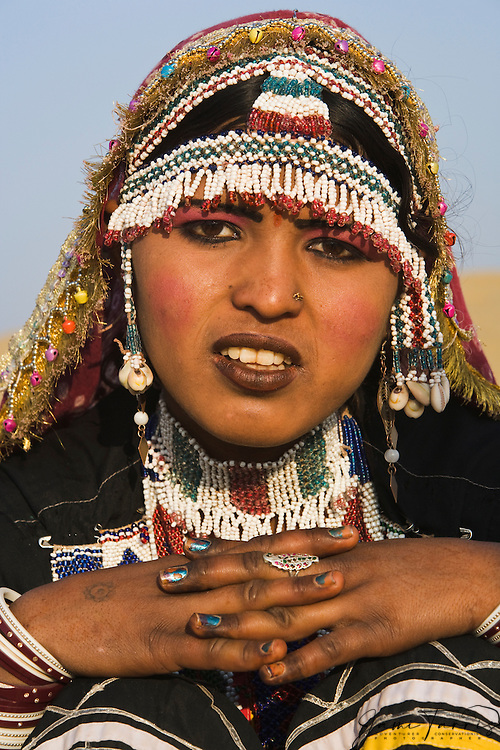 A Kalbelia tribal girl in the Thar Desert in her black tribal sari looking at the camera with a serious expression,, Thar Desert, Rajasthan, India