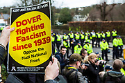 A Kent anti racism group poster (Dover fighting racism since 1939, oppose the nail national front)  is held up as Anti Facist demonstrators march through Dover protesting against a facist demonstration also taking place in the port town. 30th January 2016