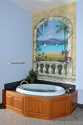 A jetted tub is surrounded by solid oak panels with a granite surface and a wonderful mural.
