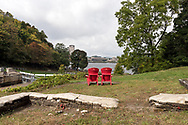 Adirondack chairs with a view of the Ottawa River and the Canadian Museum of History (Museum of Civilization) in Québec.<br /> Photographed next to Ottawa Locks 1-8 on the Rideau Canal in Ottawa, Ontario, Canada.