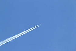 Passenger jet flies against the blue sky with a visible vapor trail