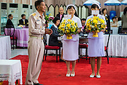 09 OCTOBER 2014 - BANGKOK, THAILAND: Nurses at Siriraj Hospital carry flowers for Bhumibol Adulyadej, the King of Thailand. The King has been hospitalized since Oct. 4 and underwent emergency gall bladder removal surgery Oct. 5. The King is also known as Rama IX, because he is the ninth monarch of the Chakri Dynasty. He has reigned since June 9, 1946 and is the world's longest-serving current head of state and the longest-reigning monarch in Thai history, serving for more than 68 years. He is revered by the Thai people and anytime he goes into the hospital thousands of people come to the hospital to sign get well cards.   PHOTO BY JACK KURTZ