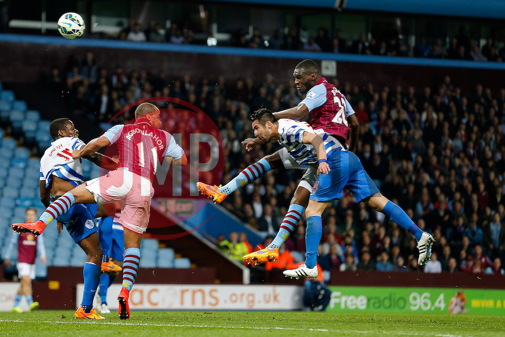 Christian Benteke of Aston Villa heads a shot as Mauricio Isla of QPR xhallenges - Photo mandatory by-line: Rogan Thomson/JMP - 07966 386802 - 07/04/2015 - SPORT - FOOTBALL - Birmingham, England - Villa Park - Aston Villa v Queens Park Rangers - Barclays Premier League.