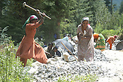 India, Manali, Kullu District, Himachal Pradesh, Northern India, women at work at a stone quarry, breaking rocks into gravel with a hammer.