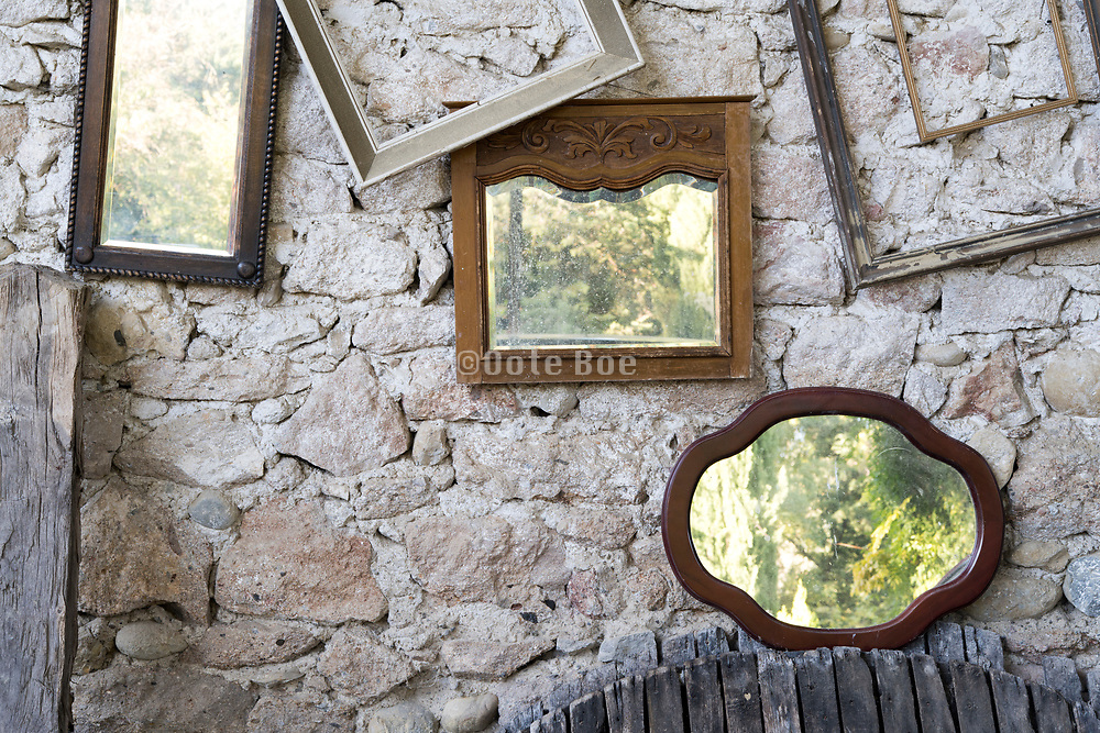 empty picture frames and mirros against a rustic stone wall