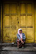 Portret van een vrouw zittend voor een oud koloniaal gebouw, Malang