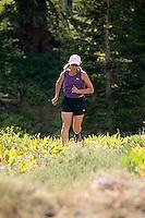 Young woman trail running through wildflowers at Kirkwood Resort. Lake Tahoe, CA