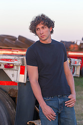 Good looking twenty something year old man in a black tee shirt and jeans outdoors leaning against part of a flatbed truck