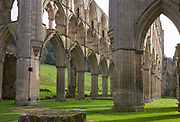 Gothic architecture ruins of the Cistercian order's Rievaulx Abbey in North Yorkshire. Tall columns, pillars and arches rise majestically from the green grass that  for centuries, was the home for successive monks and abbots who endured piety through hardship. Rievaulx was one of the first Cistercian abbeys to be founded in England. Surrounded by a massive agricultural and industrial estate, staffed by lay brothers, it was intended as the focus of a substantial family of daughter houses throughout northern Britain. Destroyed by the commissioners of King Henry VIII during the Dissolution of the abbeys and monasteries in 1538, the shattered abbey ruins became a popular subject for Romantic artists in the 18th and 19th centuries.