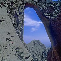 Sam Lightner (tiny) scrambles below huge Shipton's Arch  in the Kara Tagh Mountains near  Kashgar & the Taklimakan Desert in Xinjiang, China.