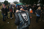 A punk wears an Exploited poster on his denim west over his leather jacket, London,Great Britain, 3rd of September 2016. He is talking close-up with a friend in front of the stage in the rain.