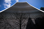 """City of London England UK March 2021<br />20 Fenchurch Street also known as the Walki Talkie building.<br />Wikipedia: 20 Fenchurch Street is a commercial skyscraper in London that takes its name from its address on Fenchurch Street, in the historic City of London financial district. It has been nicknamed """"The Walkie-Talkie"""" because of its distinctive shape.[4] Construction was completed in spring 2014, and the three-floor """"sky garden"""" was opened in January 2015.[5] The 38-story building is 160 m (525 ft) tall. Since July 2017, the building has been owned by Lee Kum Kee Groups.<br /> <br /> Designed by architect Rafael Viñoly and costing over £200 million, 20 Fenchurch Street features a highly distinctive top-heavy form which appears to burst upward and outward. The entrance floor and 34 floors of office space are topped by a large viewing deck. A bar and restaurants are included on the 35th, 36th and 37th floors; these are, with restrictions, open to the public."""