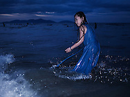 A young Vietnamese girl wades in the ocean at dusk while wearing a long blue dress, Hoi An, Vietnam, Southeast Asia