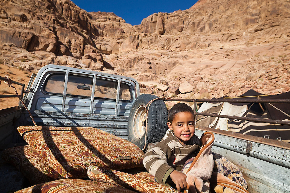 A young Bedouin boy lays down in the back of a pickup truck at his family's remote home encampment in Wadi Rum, Jordan.