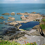 View of tunnels beach Tidal Pool from Beacons Castle, Ilfracombe, Devon, UK. Until the 1950s and the rise of the heated indoor swimming pool, children learnt to swim outdoors. For those close to the sea, many man-made tidal swimming pools were constructed around Britain's coastline. Heated by the sun, these tidal pools were often built to keep bathers safe from high and rough seas, which explains why so many of them are clustered in Scotland and around the surfing beaches of Cornwall. Whether they are simple swimming holes made by shoring up natural rock pools or grand lido-like pools complete with lifeguards and tea huts, they are all refreshed by good high tides.