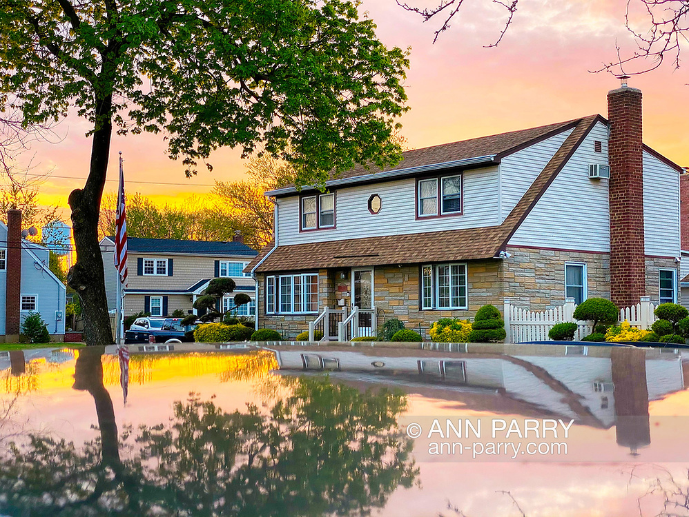 Garden City Park, New York, U.S. May 2, 2020. During my social distancing visit to Bob, I capture colorful sunset from his front yard, with scene reflected on roof of truck parked at curb