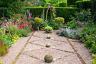 Herbaceous borders surrounding a bed of gravel and stone in the Bishop's Garden at Cothay Manor, Greenham, Wellington, Somerset, UK