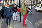 Man listening to music on his headphones wearing red trousers in the City of London, UK.