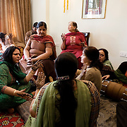 New Delhi, India, January 20, 2011. Marriage of Sumedha and Sapan. The day before the function all the women of the family gather at the bride's house for the henna ceremony. Sumedha remains seated three hours waiting for her hands and feet to be decorated by skilled artisans.