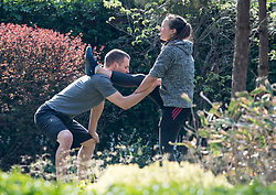 © Licensed to London News Pictures. 28/03/2020. London, UK. A woman exercising very closely with a personal trainer at Paddington Recreation Ground in London, during a lockdown over the spread of COVID-19. Prime Minister Boris Johnson has announced that people should only leave their homes for essential work, groceries, medical necessity and exercise. Photo credit: Ben Cawthra/LNP